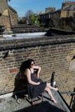 Muchacha en el vestido negro del lunar que se sienta en el balcón imagen de archivo
