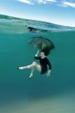 Muchacha en el vestido negro subacuático Fotos de archivo
