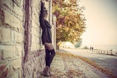 Muchacha en el vestido negro, tiempo del otoño en la ciudad imagenes de archivo