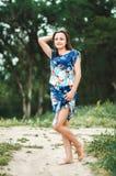 Muchacha en el vestido que se coloca con el fondo del bosque Imagenes de archivo