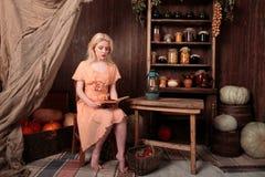 Muchacha en el vestido que se sienta en libro de lectura del sitio y soñador Fotografía de archivo libre de regalías