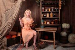 Muchacha en el vestido que se sienta en libro de lectura del sitio y soñador Foto de archivo libre de regalías