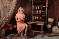 Muchacha en el vestido que se sienta en libro de lectura del sitio y soñador Imágenes de archivo libres de regalías