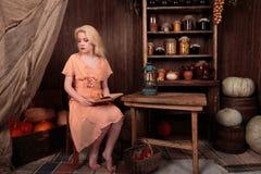 Muchacha en el vestido que se sienta en libro de lectura del sitio y soñador Imagen de archivo libre de regalías