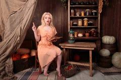 Muchacha en el vestido que se sienta en libro de lectura del sitio y soñador Imagen de archivo