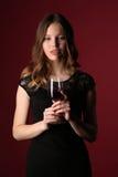 Muchacha en el vestido que sostiene el vidrio de vino Cierre para arriba Fondo rojo oscuro Fotografía de archivo libre de regalías