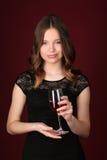 Muchacha en el vestido que sostiene la copa Cierre para arriba Fondo rojo oscuro Foto de archivo libre de regalías