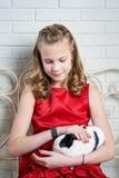 Muchacha en el vestido rojo que sostiene el conejo en sus brazos Foto de archivo
