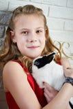 Muchacha en el vestido rojo que sostiene el conejo en sus brazos Imagen de archivo