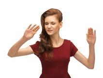 Muchacha en el vestido rojo que trabaja con algo imaginario Fotografía de archivo libre de regalías