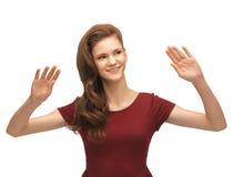 Muchacha en el vestido rojo que trabaja con algo imaginario Imagen de archivo libre de regalías