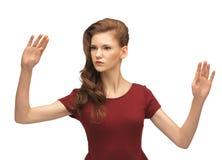 Muchacha en el vestido rojo que trabaja con algo imaginario Fotografía de archivo