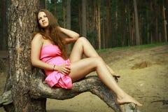 Muchacha en el vestido rosado que se relaja en el claro del bosque, entre pinos. Foto de archivo