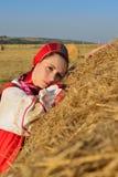 Muchacha en el vestido ruso en el heno Imagen de archivo libre de regalías