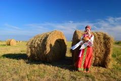 Muchacha en el vestido ruso en el heno con pan Imagen de archivo