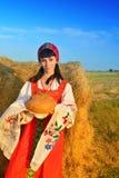 Muchacha en el vestido ruso en el heno con pan Fotos de archivo libres de regalías