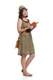 Muchacha en el vestido y el sombrero del verano que sostienen la guía turística Fotografía de archivo libre de regalías