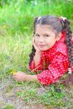 Muchacha en el windbreaker rojo que miente en la hierba Imágenes de archivo libres de regalías