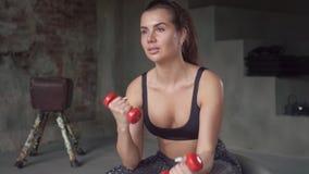 Muchacha en entrenamiento negro de la ropa de deportes con pesas de gimnasia mientras que se sienta en suizo-bola en el fondo de  almacen de metraje de vídeo