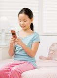 Muchacha en envío de mensajes de texto de los pijamas con el teléfono celular Imagenes de archivo