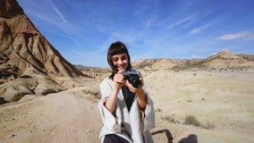 Muchacha en equipo tradicional en desierto con la cámara metrajes