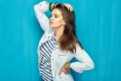 Muchacha en estilo adolescente con el pelo largo que se opone al CCB azul de la pared Fotografía de archivo