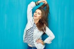 Muchacha en estilo adolescente con el pelo largo que se opone al CCB azul de la pared Imagen de archivo libre de regalías