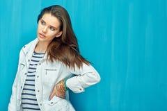 Muchacha en estilo adolescente con el pelo largo que se opone al CCB azul de la pared Imagenes de archivo