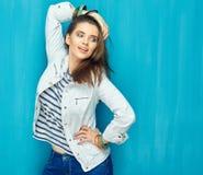 Muchacha en estilo adolescente con el pelo largo que se opone al CCB azul de la pared Fotos de archivo