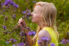 Muchacha en flores púrpuras al aire libre en verano Imagen de archivo