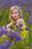 Muchacha en flores púrpuras al aire libre en verano Foto de archivo libre de regalías