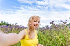 Muchacha en flores púrpuras al aire libre en verano Fotos de archivo libres de regalías