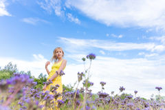 Muchacha en flores púrpuras al aire libre en verano Imagenes de archivo