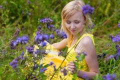 Muchacha en flores púrpuras al aire libre en verano Imagen de archivo libre de regalías