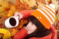Muchacha en follaje anaranjado del otoño con la taza de café Imagenes de archivo