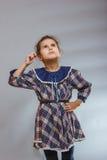 Muchacha en fondo gris en un vestido que mira para arriba Foto de archivo