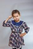 Muchacha en fondo gris un vestido profundamente en pensamiento Imagenes de archivo