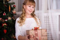 Muchacha en frente el árbol de navidad que sostiene un regalo Foto de archivo