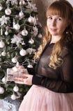 Muchacha en frente el árbol de navidad que sostiene un regalo Imagenes de archivo
