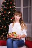 Muchacha en frente el árbol de navidad que sostiene un regalo Imágenes de archivo libres de regalías