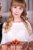 Muchacha en frente el árbol de navidad que sostiene un regalo Imagen de archivo libre de regalías