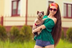 Muchacha en gafas de sol con el yorkie del perro en las manos Imágenes de archivo libres de regalías