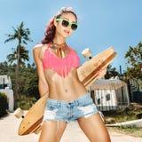 Muchacha en gafas de sol con longboard Imagen de archivo libre de regalías