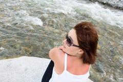 Muchacha en gafas de sol en la orilla del río fotografía de archivo libre de regalías