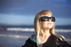 Muchacha en gafas de sol en la playa Foto de archivo libre de regalías