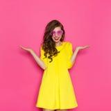 Muchacha en gafas de sol rosadas con la mano aumentada Foto de archivo