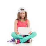 Muchacha en gorra de béisbol usando la tableta digital Fotos de archivo