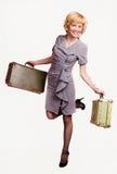 Muchacha en gris con bagaje Imagen de archivo libre de regalías