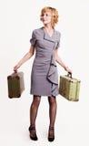 Muchacha en gris con bagaje Imagenes de archivo
