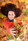 Muchacha en grupo anaranjado de la hoja del otoño con la baya. Imagen de archivo libre de regalías